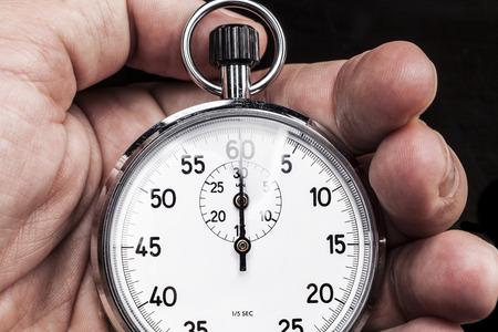 chronometer: Chronometer in hand isolated on black background Stock Photo