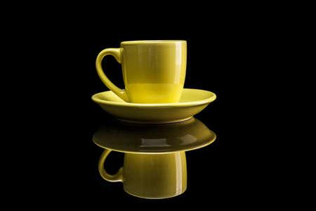 reflexion: Taza amarilla aislada en el fondo negro con la reflexi�n