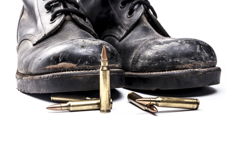 shoe string: Bullets and army boots isolated on white background with shadow