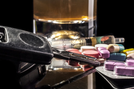 intoxicate: Car keys and pills isolated on black background with reflection Stock Photo