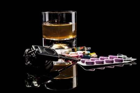 intoxicate: Alcohol, pills and car keys isolated on black background with reflection