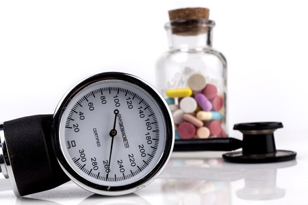 sphygmomanometer: Colored Pills in a Jar with Sphygmomanometer and Black Stethoscope