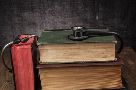 auscultate: Old Books on Wood Table with Black Stethoscope Stock Photo