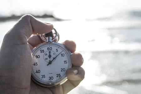 Cronómetro analógico a mano con mar de fondo Foto de archivo