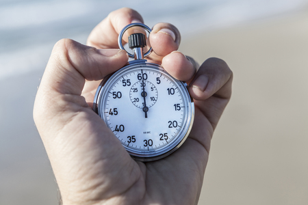 chronometer: Hand holding a chronometer and sea in background Stock Photo