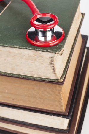 red stethoscope: Red Stethoscope on Old Books Pile on White Background