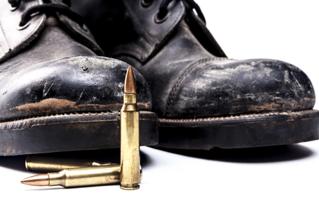 shoe string: Army boots and bullets isolated on white background with shadow
