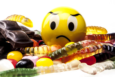 jellybean: Sad emoticon eating sweets on white background