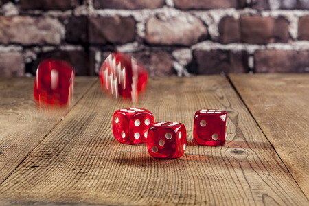 red dice: Falling red dice on brown wood table Stock Photo