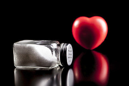 Heart and salt isolated on black background with reflection Stock Photo