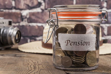 pension cuts: Coins in jar on wood table and brick background