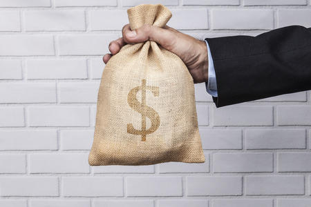 spending full: Hand holding a sack of money and white brick background