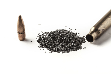 Bullet and gunpowder isolated on white background with shadow