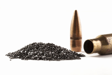 Rifle Bullet and Shel near pile of gunpowder isolated on white