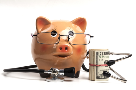 Cute Piggy Bank With Black Stethoscope and Dollars Roll Banknotes Isolated on White Background