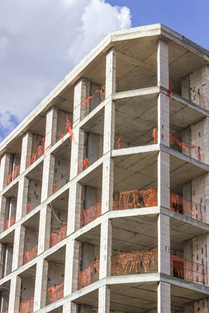 Vertical perspective shot of colorful construction of a new reinforced concrete building with open blue sky