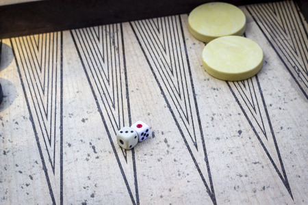 Perspective shoot of dices on backgammon under open light with play stones