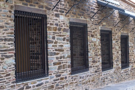 Perspective shoot of iron bar windows on masonry old inn in local places of Turkey
