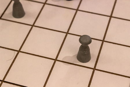 Close perspective shoot of wooden big size checkers and figures under clean light