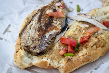 Close-up shoot of fish and bread food on the street Imagens