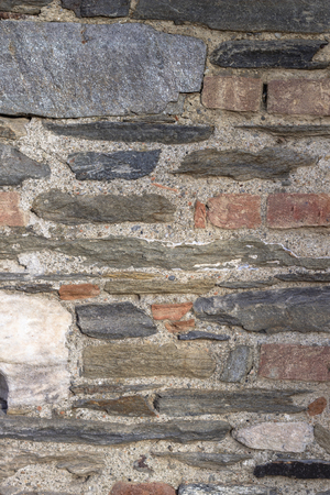 Vertical framed of masonry colorful stone wall as texture sample