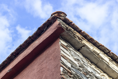 Close shoot of masonry building roof corner with blue open sky background