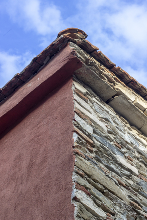 Vertical frame shoot of masonry building roof corner with blue open sky background Imagens