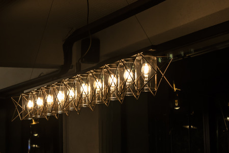 Array of clear light chandeliers under dark atmosphere Imagens