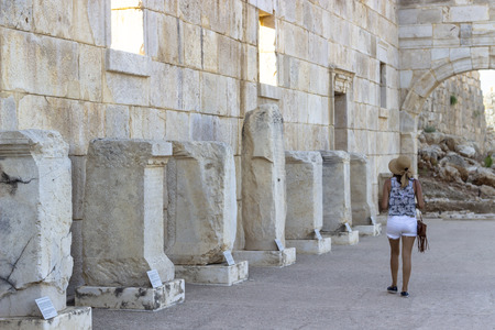 Woman promenades in the ancient historical structures and observe old columns information Imagens