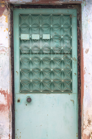 Front shoot of traditional green metal door in turkish village