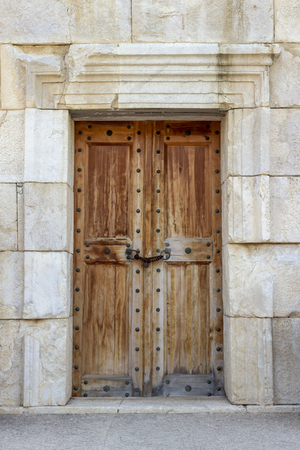 Front shoot of ancient civilization made wooden door on historical stone building Imagens