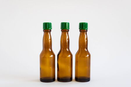 Front close-up shoot of three small alcohol bottles brown colored