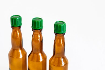Close-up corner shoot of three line positioned small alcohol bottles brown colored
