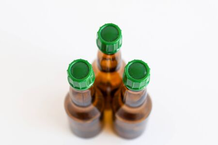 Top shoot of three triangled positioned small alcohol bottles brown colored Stok Fotoğraf
