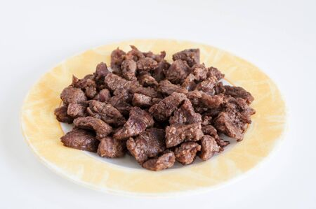 Close-up shoot of tasty meat on small plate with white background