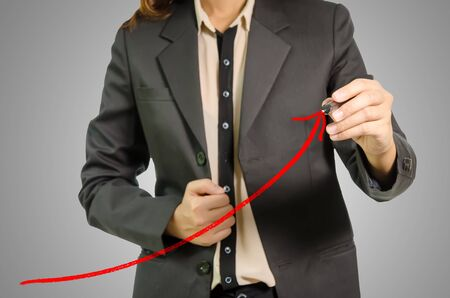population growth: Business woman drawing a red graph, focus is on graph with Gray Background. Stock Photo