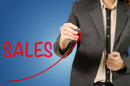sales growth: Business woman pointing rising Growth Sales drawn on Blue Background. Stock Photo