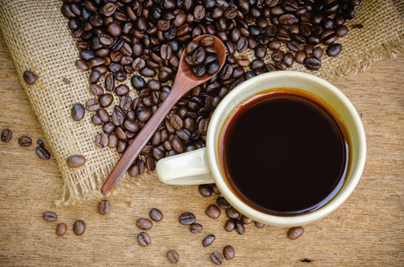 americano: Cup of Americano coffee and coffee beans on wooden background