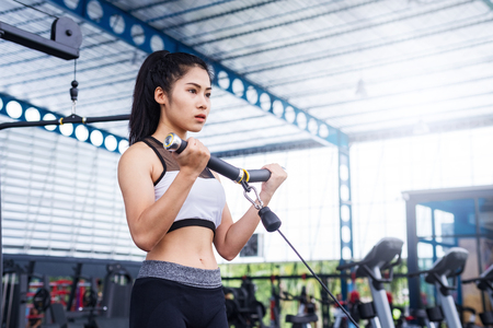 fitness woman exercise workout with exercise-machine Cable in fitness gym. healthy lifestyle Concept