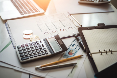 Accounting cryptocurrencies investors of bitcoins with documents and calculator in background.
