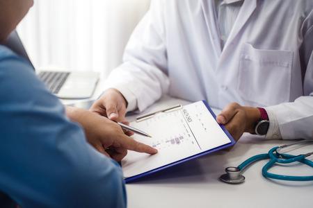 El médico explica el documento de control de salud del paciente masculino en la clínica médica o la salud del hospital. concepto de salud y médico. Foto de archivo