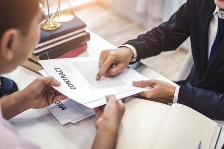 Mannelijke advocaat legt een contractovereenkomst uit aan cliënt voor wet. Wet en juridische dienstenconcept.