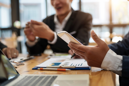 Business man using phone while meeting for share financial report in conference room . Accounting concept. 版權商用圖片