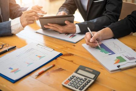 Gruppe von Geschäftsleuten, die mit Laptop und Tablat und Papierdiagramm im Büroraum arbeiten. Buchhaltungskonzept.