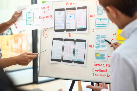 UX designer creative group working about planing mobile application project with sticky notes. User experience concept.