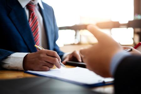 Gli uomini d'affari discutono e negoziano investimenti immobiliari con la firma di un contratto di prestito a termine in ufficio. contratto e concetto di accordo. Archivio Fotografico
