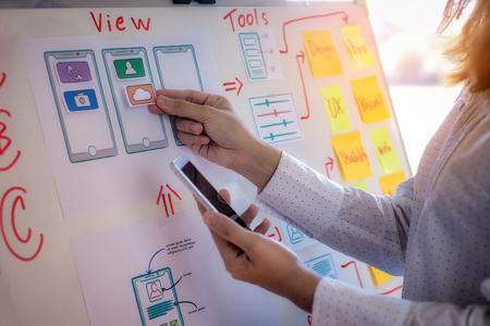 Webdesignerfrau, die Testskizzenzeichnungsanwendung für Handy im Büro tut. Benutzererfahrung Designkonzept.
