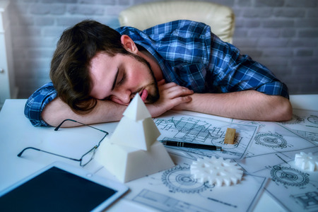 Engineering man working overwork and sleep on the desk with blueprint mechanical parts in office. having a bad stress and overwork concept - Image 스톡 콘텐츠