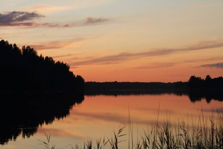 Reflected in the water of the forest lake late sunset summer evening. Valdai national Park.