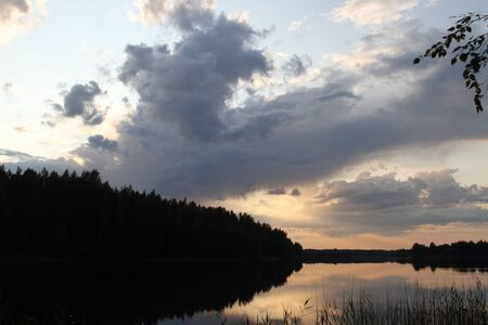 Clouds over  the forest lake late sunset summer evening. Valdai national Park.